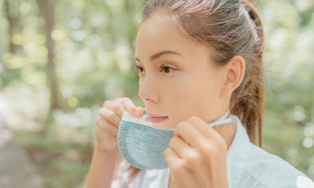 Female Asian removing mask exposing acne