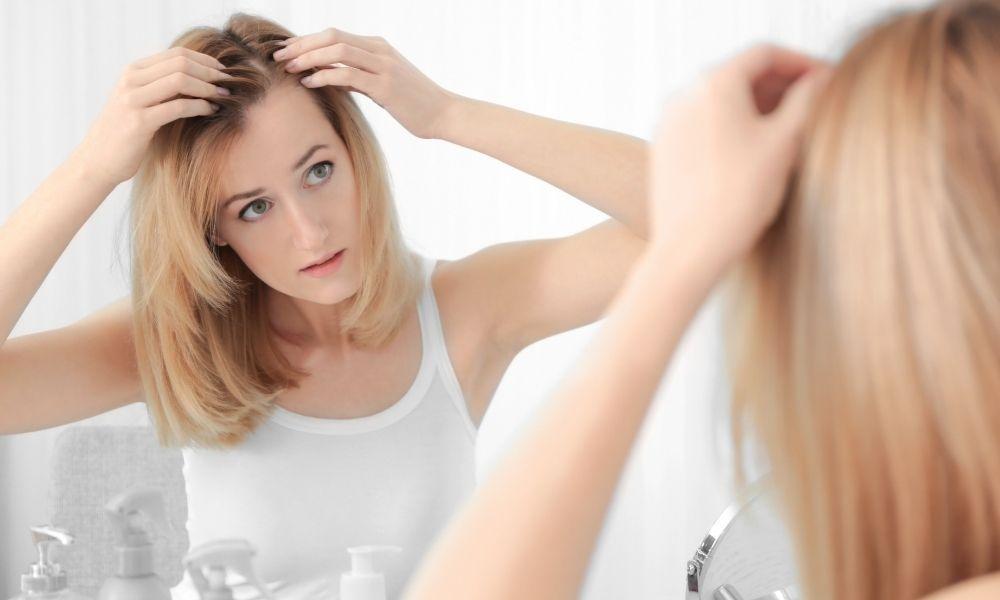 caucasian female examining thinning hair