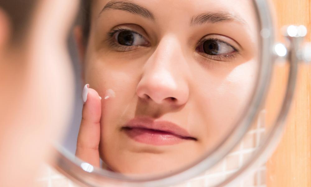 white female examining skin in the mirror