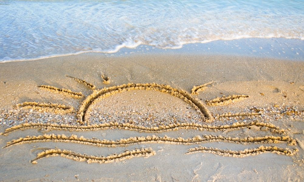 Sun and Waves etched into the sand on a beach