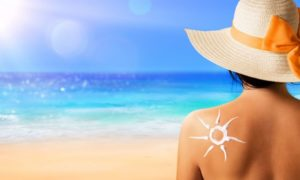 Sun Safety Tips Caucasian Female at beach with sunscreen